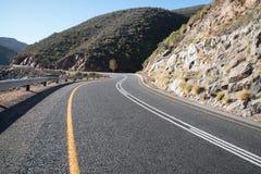 Slingrig tjäraväg i bergen Arkivfoto