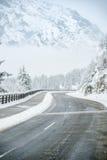 Slingrig väg till och med ett dolt berg för snö arkivfoto