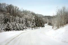 Slingrigt landskap för landsväg i vintersnö fotografering för bildbyråer