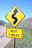 Slingrigt vägmärke Arkivfoto