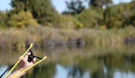 Slingshot. Little boy shooting slingshot into a lake Stock Image