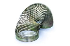 Slinky metal helix spring stretched open with both ends resting on surface, on white background royalty free stock images