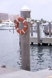 Slip 12 - Boat Dock with Life Saver. Luxury Boat slip number 12 dockside in the Bahamas with small dingy and large ocean liners in background royalty free stock images