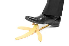 Slip banana. Business boot to step on a banana skin on a white Stock Photography