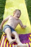 Slip N Slide. Young boy playing on slip and slide in summer laughing stock images