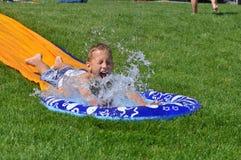 Slip and Slide. Boy splashing into water at end of slip-n-slide in backyard Royalty Free Stock Images