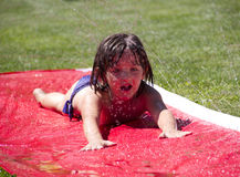 Slip and Slide. Gilr slides across a slip and slide on the grass in the Summer Stock Images