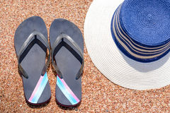 Slip slops and sunhat on a tropical beach. Overhead view of a pair of casual slip slops and sunhat on a tropical beach conceptual of a summer holiday or vacation Royalty Free Stock Photography