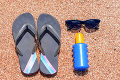 Slip slops sunscreen and sunglasses on a beach. Overhead view of a pair of slip slops sunscreen and sunglasses on a beach neatly laid out on golden sand on a Stock Photos