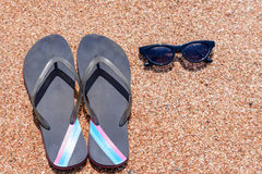 Slip slops sunscreen and sunglasses on a beach. Overhead view of a pair of slip slops and sunglasses on a beach neatly laid out on golden sand on a beach Stock Photography
