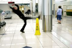 Slipped. Man slips next to Wet Floor sign stock image