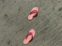 Slippers. A pair of slippers on beach sand Royalty Free Stock Photo