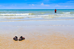 Slippers on beach. Slippers and angler on background out of focus Stock Photography
