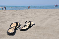 Slippers on beach. Female slippers on a beach of the mediterranean sea Royalty Free Stock Photos