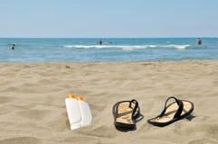 Slippers on beach. Female slippers and sun cream on beach stock photo Royalty Free Stock Photos