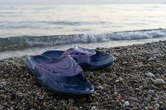 Slippers on the Beach. Blue slippers on a pebble beach against blue sea horizon Royalty Free Stock Photos