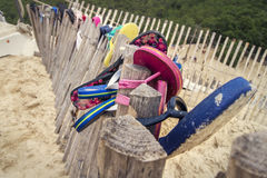 Slippers on the beach. Some slippers or flip-flops hanging on a wooden fence at the beach Royalty Free Stock Photos