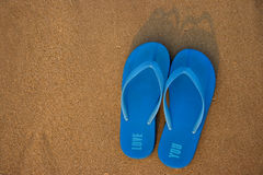 Slippers. Blue slippers on sandy beach Stock Photography
