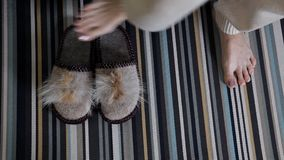 Slippers on the carpet. The girl puts on home shoes. Comfort, warm.  stock video footage