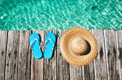 Slippers at jetty. Slippers and hat at jetty by the sea Stock Image