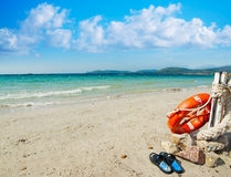 Slippers and life buoy by the shore in Alghero Royalty Free Stock Photos