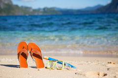 Slippers, mask and snorkel on sand beach Royalty Free Stock Photo