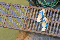 Slippers on metal gangway bridge connecting to the boat, Laos Stock Photo