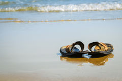 Slippers on ocean beach Stock Photo
