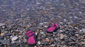 Slippers on the Pebble beach. stock footage