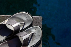 Slippers beside a pool Royalty Free Stock Images
