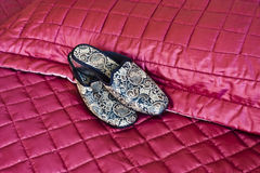 Slippers on quilt. A pair of embroided slippers on a bed quilt Stock Image