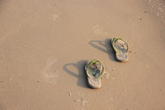 Slippers in the sand. Royalty Free Stock Image