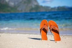 Slippers on sand beach Stock Photos