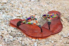 Slippers on the sand. Colorful slippers on the shell ground Royalty Free Stock Image