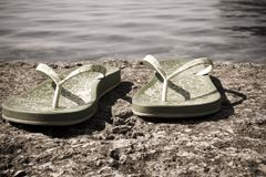 Slippers at the sea coast. Slippers at the stone sea coast Royalty Free Stock Images