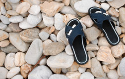 Slippers at the stone beach Royalty Free Stock Photos