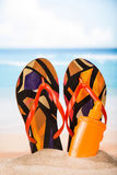 Slippers and sunblock in the sand Stock Photo