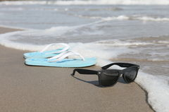 Slippers and sunglasses on the beach. Blue slippers and sunglasses summer beach ocean wave royalty free stock images