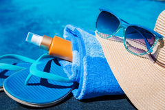 Slippers, sunsscreen cream, hat, sunglasses near swimming pool holiday concept Royalty Free Stock Images