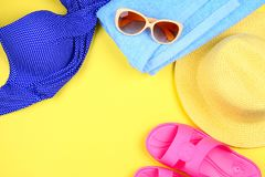 Slippers, swimsuit bikini, towel, hat and sunglasses on a pastel yellow background. Travel, sea, vacation, holiday. Slippers, swimsuit bikini, towel, hat and royalty free stock photography