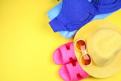 Slippers, swimsuit bikini, towel, hat and sunglasses on a pastel yellow background. Travel, sea, vacation, holiday. Slippers, swimsuit bikini, towel, hat and stock images