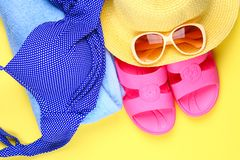 Slippers, swimsuit bikini, towel, hat and sunglasses on a pastel yellow background. Travel, sea, vacation, holiday. Slippers, swimsuit bikini, towel, hat and stock photos