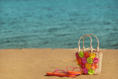 Slippers with wicker bag on the beach Stock Photos