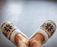Slippers on women`s legs. Soft comfortable home slipper Stock Photo