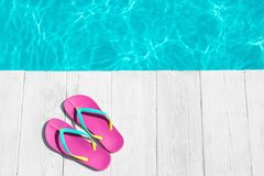 Slippers on wooden deck near swimming pool, space for text. Beach accessory. Slippers on wooden deck near swimming pool, top view with space for text. Beach stock photography