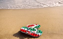 Slippers with the word Italy on beach sand - holidays and relaxation concept Stock Image