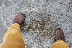 Slippery asphalt road. Top view of male legs on slippery asphalt road royalty free stock photo