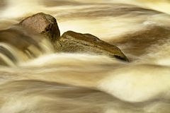 Slippery boulders in mountain stream. Clear water blurred by long exposure, low water level. Stock Photography