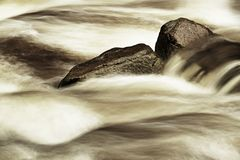 Slippery boulders in mountain stream. Clear water blurred by long exposure, low water level. Stock Photos