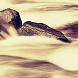 Slippery boulders in mountain stream. Clear water blurred by long exposure, low water level. Stock Photo